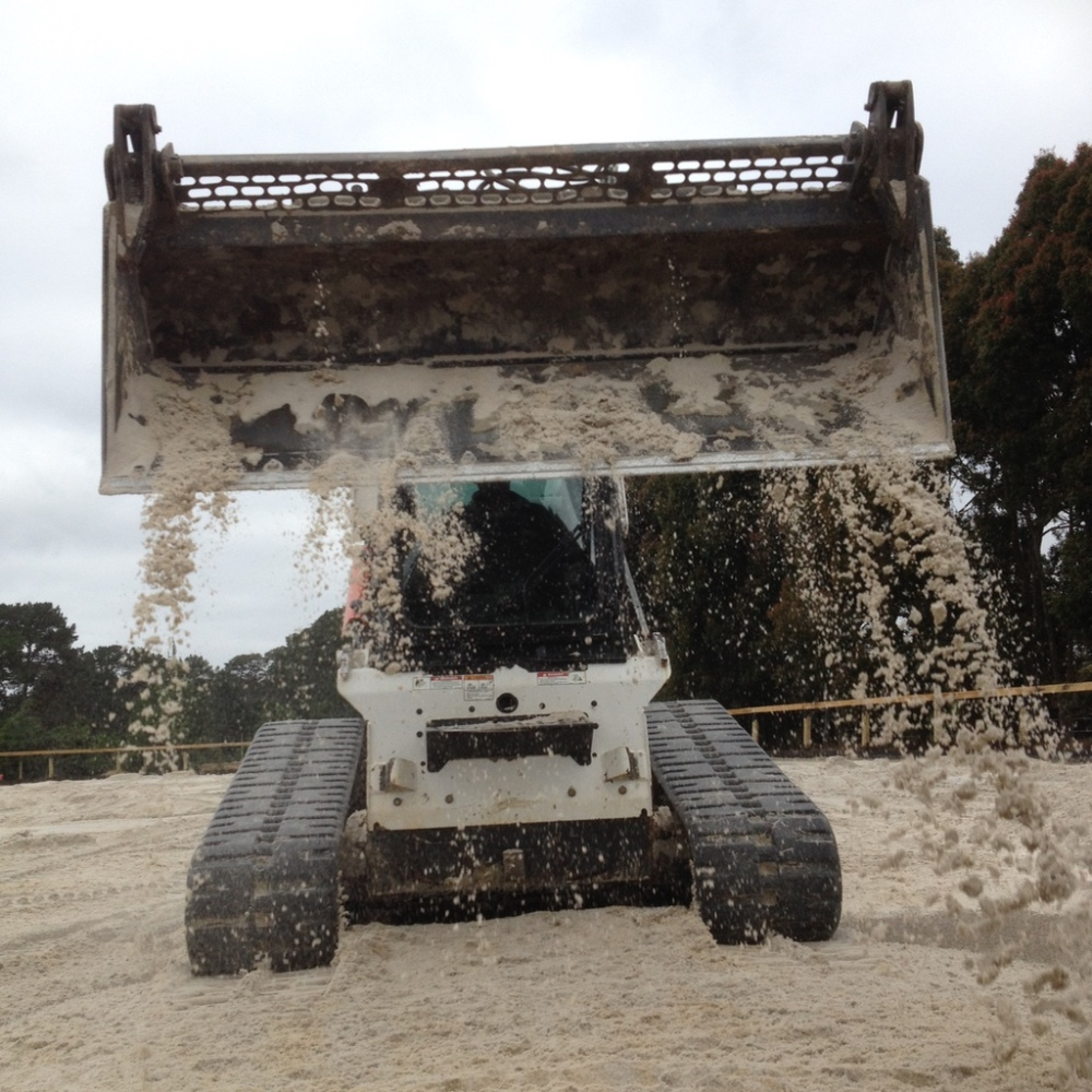Spreading sand on dressage arena
