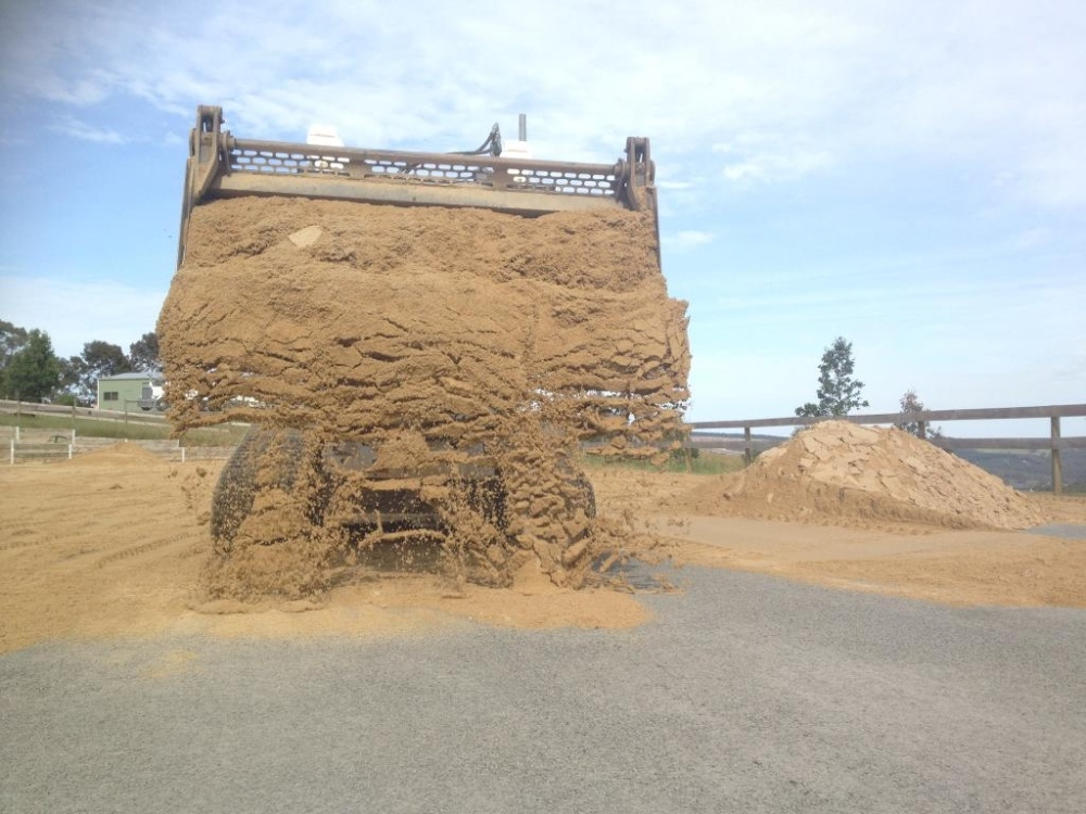 Spreading sand on horse arena